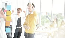 Group of business persons looking at work on a glass. Board and cheering with colleagues in the background Stock Images