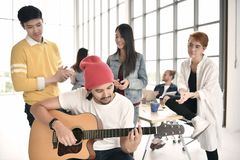 Group of business persons relaxing. Playing guitar and chatting during break time at the office Royalty Free Stock Photos