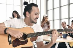 Group of business persons relaxing. Playing guitar and chatting during break time at the office Stock Image