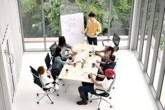 Group of business persons sitting around a desk. Listening to and discussing about a presentation by a colleague at the office Royalty Free Stock Photography