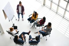 Group of business persons. Sitting in circle listening, questioning and paying attention to a presentation by a colleague Stock Photography