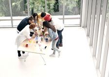 Group of business persons standing around a desk. Brainstorming and discussing work at the office Royalty Free Stock Images