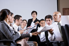 Group business presentation handing out papers Royalty Free Stock Photos