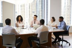 Group Of Business Professionals Meeting Around Table In Modern Office stock image