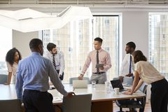 Group Of Business Professionals Standing At Meeting Around Table In Modern Office royalty free stock photos