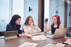 Group of business women meeting in a meeting room with blank scr. Een, sharing their ideas, Multi ethnic Royalty Free Stock Photography