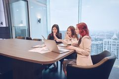 Group of business women meeting in a meeting room with blank scr. Een, sharing their ideas, Multi ethnic Royalty Free Stock Photo