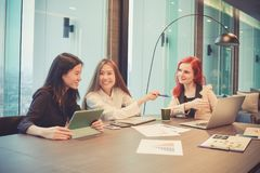 Group of business women meeting in a meeting room with blank scr. Een, sharing their ideas, Multi ethnic Royalty Free Stock Photos