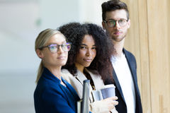 Group of business young people looking at camera in a hallway of the company. Stock Images