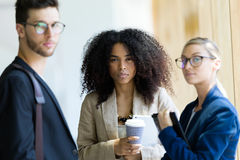Group of business young people looking at camera in a hallway of the company. Stock Image