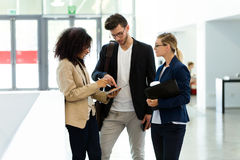 Group of business young people using the digital tablet in a hallway of the company. Royalty Free Stock Photography