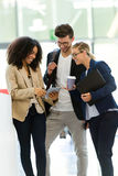 Group of business young people using the digital tablet in a hallway of the company. Royalty Free Stock Photo