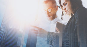 Group of businessmans on meeting.Business team in working process.Double exposure,skyscraper building blurred background. Flares effect Stock Photo