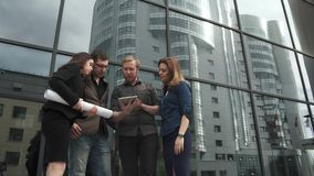 Group of businessmen background a modern office building. The manager shows the project on the screen of the tablet stock video footage