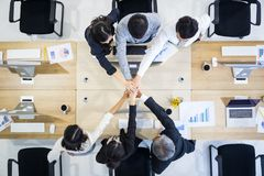 Group of businessmen and businesswomen standing and stacking han stock photography