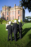 Group of businessmen in hardhats with blueprint looking at manor house, rear view Royalty Free Stock Photo