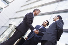 Group of businessmen shaking hands outside office. Group of businessmen shaking hands outside modern office Royalty Free Stock Photo