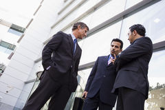 Group of businessmen talking outside office. Group of businessmen talking outside modern office Royalty Free Stock Photo