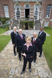 Group of businessmen and woman by manor house, portrait, elevated view Stock Photos