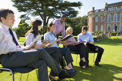 Group of businessmen and women in training course outdoors by manor house Stock Photo