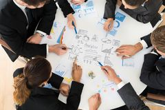 Group of businesspeople analyzing graph. High Angle View Of Businesspeople Analyzing Graph In Office stock image