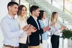 Businesspeople clapping in office. Group of businesspeople clapping in office royalty free stock images