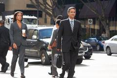 Group Of Businesspeople Crossing Street. Smiling Stock Image