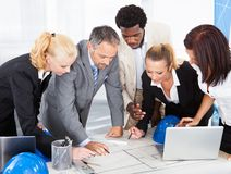 Group of businesspeople discussing together. Group Of Happy Multiracial Businesspeople Discussing Together In Office stock images