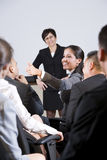 Group businesspeople, focus on woman in audience. Group of businesspeople, focus on woman in audience speaking Royalty Free Stock Images
