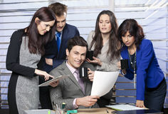 Group of businesspeople with happy leader in office. Group of friendly businesspeople with happy leader in office Stock Images