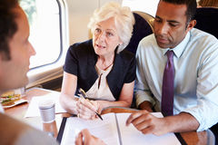 Group Of Businesspeople Having Meeting On Train stock image