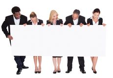 Group of businesspeople holding placard Stock Image