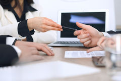 Group of businesspeople or lawyers discussing contract papers and financial figures while sitting at the table. Close-up. Of human hands at meeting or Stock Photography
