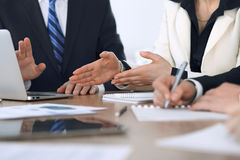 Group of businesspeople or lawyers discussing contract papers and financial figures while sitting at the table. Close-up. Of human hands at meeting or stock images