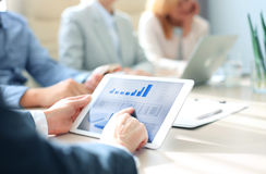 Group of businesspeople looking at graphs. Cropped shot of a group of businesspeople looking at graphs on digital tablets Royalty Free Stock Images