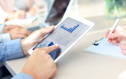 Group of businesspeople looking at graphs. Cropped shot of a group of businesspeople looking at graphs on digital tablets Royalty Free Stock Photos