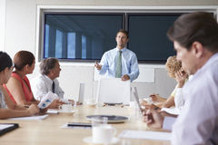 Group Of Businesspeople Meeting Around Boardroom Table Stock Photos