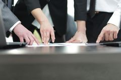 Close-up of male and female hands pointing at business document. Group of businesspeople pointing to a document on a desk, close up cropped view of their hands Royalty Free Stock Images
