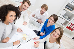 Group of businesspeople seated around a table. Group of happy multiethnic young businesspeople seated around a table at the office pausing in their meeting to stock photography