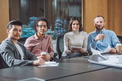 group of businesspeople sitting in conference room together and looking stock image