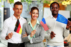Group of businesspeople standing with flags. Happy group of businesspeople standing with flags in office stock photography