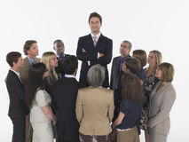 Group of Businesspeople Staring At Tall Man Stock Images