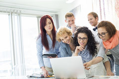 Group of businesspeople using laptop at desk in creative office Royalty Free Stock Photo
