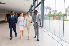 Group of businesspeople walking. Group of professional businesspeople walking in office building Stock Image