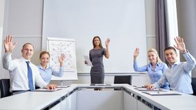 Group of businesspeople waving hands in office. Business, people and teamwork concept - group of smiling businesspeople meeting and waving hands in office royalty free stock image