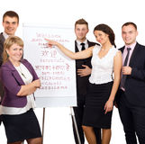 Group of Businesspeople welcome Customers on white Background. Group of smiling Business People welcoming Customers at flip chart with word WELCOME written in Royalty Free Stock Photo