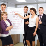 Group of Businesspeople welcome Customers on white Background. Group of smiling Business People welcoming Customers at flip chart with word WELCOME written in Royalty Free Stock Image