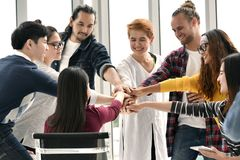 Group of businesspersons stacking hands together in agreement in a meeting stock photography