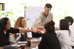 Group of business persons stacking hands together in agreement in a meeting at office royalty free stock photo