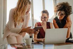 Group of businesswoman working over a new project. Three beautiful creative business women working with laptop and watching something on tablet in office. Group stock image